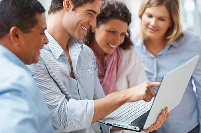 Buy stock photo Happy male executive pointing at laptop screen to colleagues