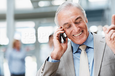 Buy stock photo Happy elderly man speaking over cellphone with colleagues at the back