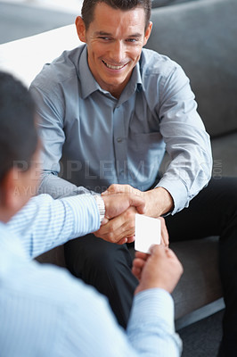 Buy stock photo Business deal in an office - Business men exchanging businesscard with a handshake