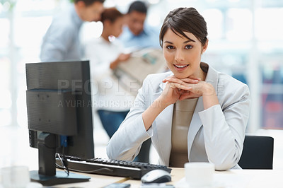 Buy stock photo Pretty Caucasian business woman at office desk with colleagues in the back