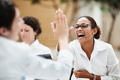 Buy stock photo Happy African American business woman giving a colleague the high five during a meeting