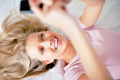 Buy stock photo Pretty happy woman sending a text message with a cell phone