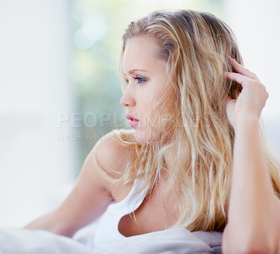 Buy stock photo Side view of a young blond woman at home looking away in thought