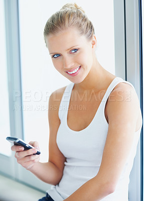 Buy stock photo Cute young female with her cellphone sitting on a window sill