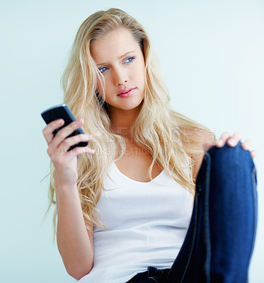 Buy stock photo Pretty young blond woman sitting against the wall with a cellphone