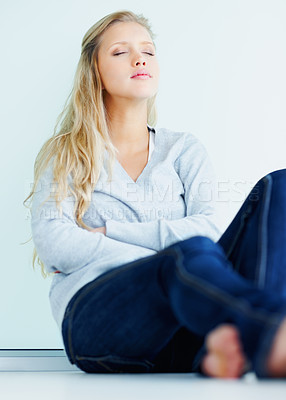 Buy stock photo Young peaceful female sitting against the wall with eyes closed