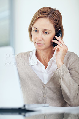 Buy stock photo Portrait of confident mature businesswoman talking on mobile while working on laptop