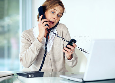Buy stock photo Portrait of surprised middle aged businesswoman multitasking by handling telephone calls working in office