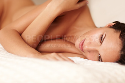 Buy stock photo An attractive young nude woman lying down on a bed