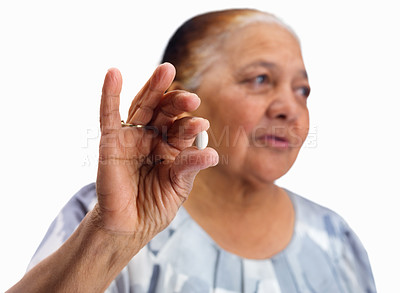 Buy stock photo Senior woman holding a pill isolated against white background