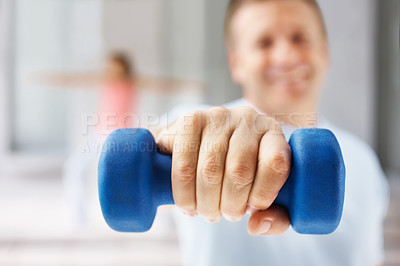 Buy stock photo Closeup of a man exercising with a dumbbell while at the gym , focus on his hand