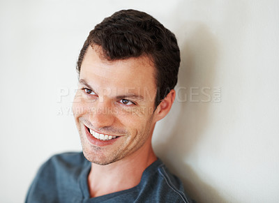 Buy stock photo Closeup of handsome young man smiling while leaning against the wall