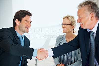Buy stock photo Senior business man giving handshake to young male executive with female colleague in background
