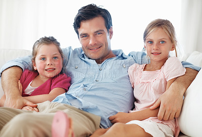 Buy stock photo Portrait of handsome man with daughters sitting on sofa
