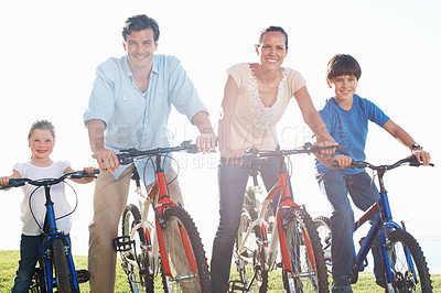 Buy stock photo Happy middle aged couple with children cycling on countryside
