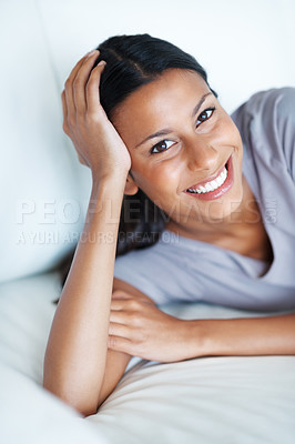 Buy stock photo Pretty mixed race woman smiling while relaxing on couch