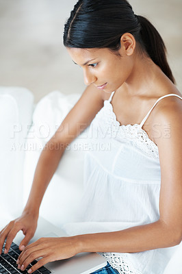 Buy stock photo Beautiful mixed race woman using laptop on couch