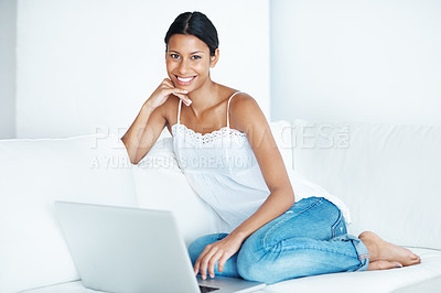 Buy stock photo Smiling mixed race woman using laptop on couch