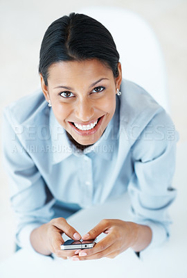 Buy stock photo High angle view of beautiful female executive text messaging on mobile phone