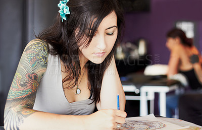 Buy stock photo A female tattoo artist drawing a new design while in her tattoo parlour