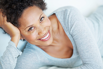 Buy stock photo Closeup of attractive African American woman smiling while lying on couch