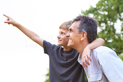 Buy stock photo Young boy hold his arm around his father's neck while pointing up into the sky