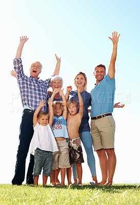 Buy stock photo Full length of three generation family cheering in park with arms raised
