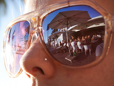 Buy stock photo A young woman enjoys the warm sun and social atmosphere reflecting in the the lens of her sunglasses