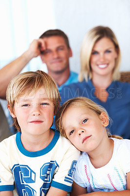 Buy stock photo Portrait of cute siblings at home with smiling parents in background