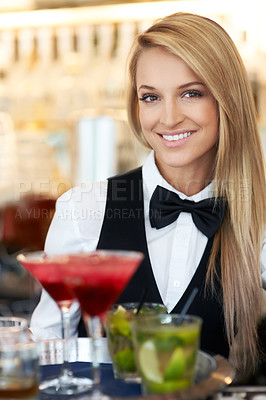 Buy stock photo Portrait of a beautiful barmaid serving cocktails at a bar/restaurant