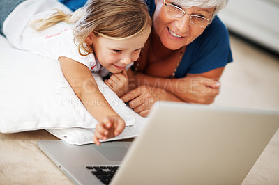 Buy stock photo Beautiful little girl using laptop with smiling grandmother at home