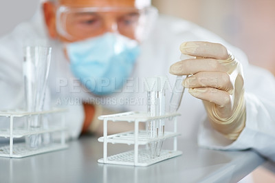 Buy stock photo Male scientist looking at a test tube of clear solution in a laboratory