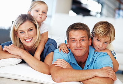 Buy stock photo Portrait of happy middle aged couple with two little kids lying on floor