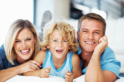 Buy stock photo Portrait of happy middle aged couple lying on floor with cute little boy at home