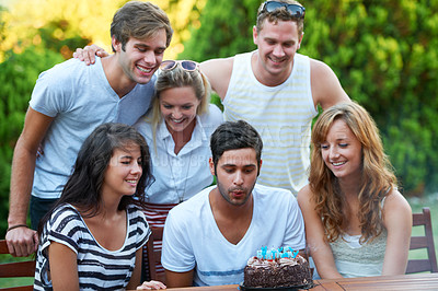 Buy stock photo Happy young teen blowing out his birthday candles with his friends in the background
