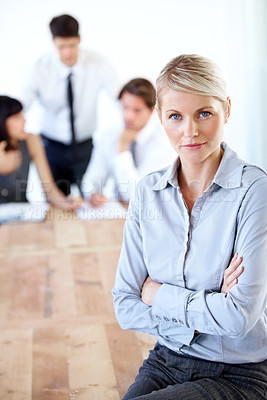 Buy stock photo Portrait of a pretty businesswoman sitting on a desk with her arms folded - blurred colleagues in the background