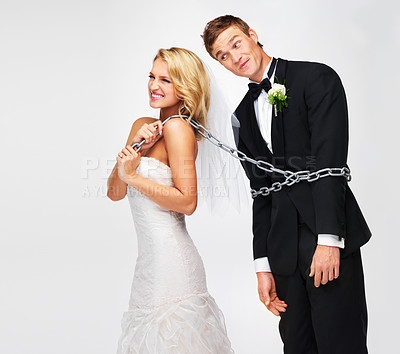 Buy stock photo Smiling young bride pulling her groom along by a chain wrapped around his waist