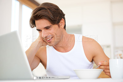 Buy stock photo A handsome young man surfing the net while eating a bowl of cereal