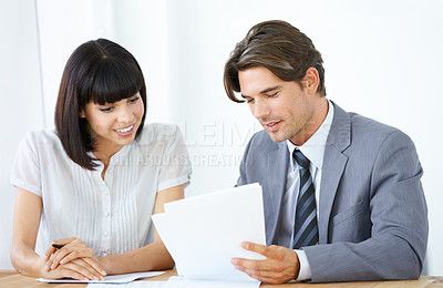 Buy stock photo Two young executives going through business documents at the office together