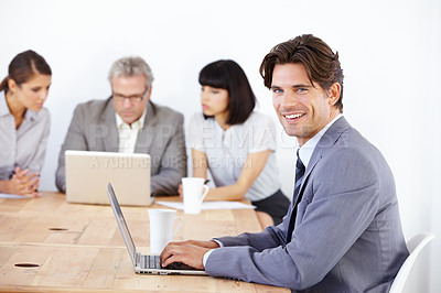 Buy stock photo Portrait of a handsome young executive working on his laptop with his team in the background