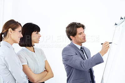 Buy stock photo Three young and ambitious executives strategizing together on a whiteboard
