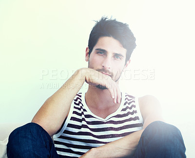 Buy stock photo Portrait of a striking young man sitting down with his hand to his mouth - Copyspace