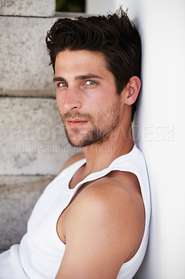 Buy stock photo Handsome young male staring at you while leaning against a wall