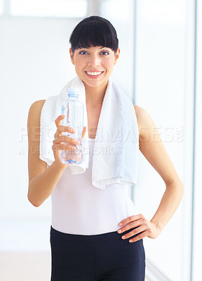 Buy stock photo Attractive young woman in fitness gear holding a water bottle