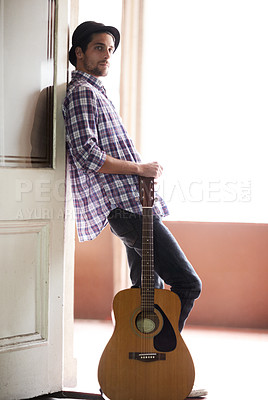 Buy stock photo A handsome young musician standing with his guitar