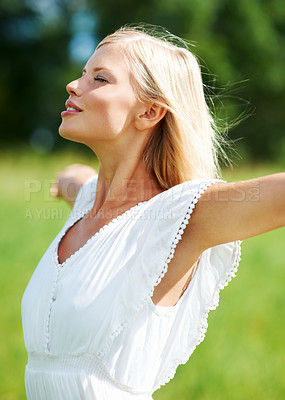 Buy stock photo Beautiful young woman standing outdoors enjoying the country air with her arms outstretched