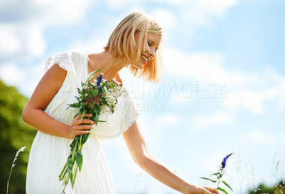 Buy stock photo Cropped view of a young woman picking flowers outdoors
