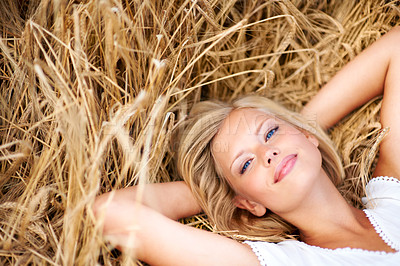 Buy stock photo Happy and smiling young woman lying in a field of wheat