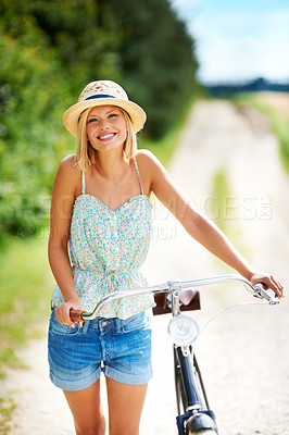 Buy stock photo Smiling young woman walking alongside her bicycle in the countryside