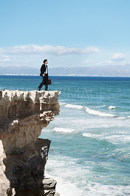 Buy stock photo Businessman standing on the edge of a cliff looking out over the ocean